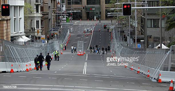 Police and pedestrians make their way past a wall of concrete and steel fences erected as a part of security for the AsiaPacific Economic Cooperation...