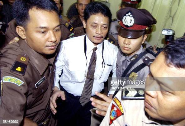 Police and prosecutors escort Garuda Indonesia pilot Pollycarpus Priyanto to a court for his trial in Jakarta 20 December 2005 over the murder of a...