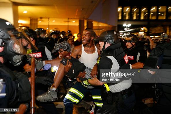 Police and protesters carry a seriously wounded protester into the parking area of the the Omni Hotel during a march to protest the death of Keith...