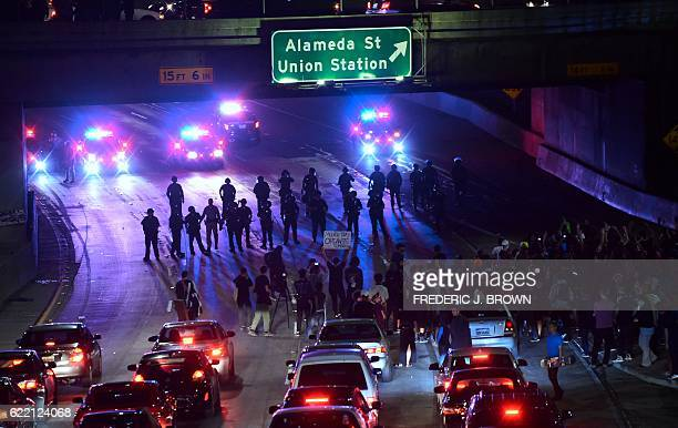 Police and protesters face off on a freeway in downtown Los Angeles California after midnight early on November 10 2016 as protesters angry over...