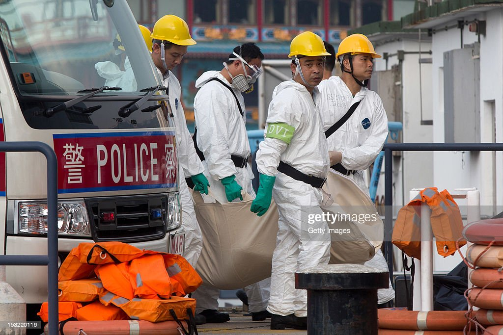 Police and rescue officers carry a body of a deceased passenger at the Marine Police Base in Aberdeen, on October 2, 2012 in Hong Kong. Thirty-six passengers have been killed and several others were injured when a Hong Kong Electric ferry, carrying 124 people, collided with a tug boat off the coast of Hong Kong late on Monday.