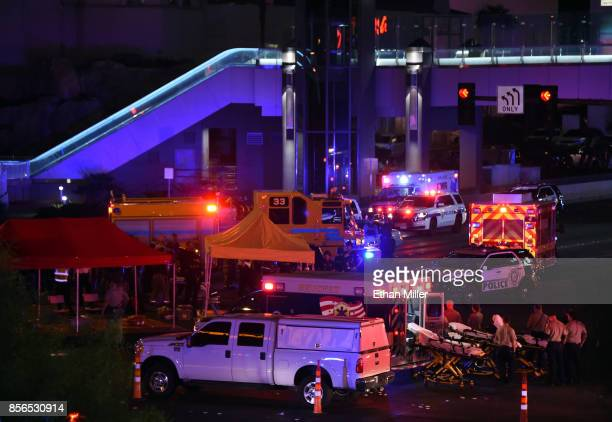 Police and rescue personnel gather at the intersection of Las Vegas Boulevard and Tropicana Ave after a mass shooting at a country music festival...