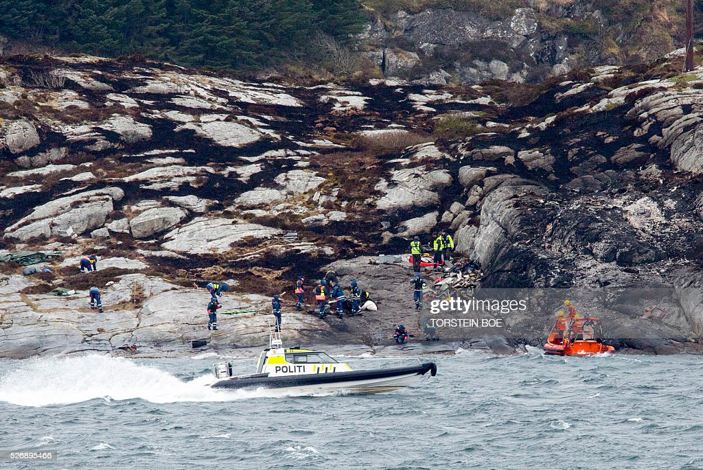 Police and rescue workers clean up at the scene where a helicopter crashed the day before on the Island of Turoy on May 1, 2016. All 13 people on board a helicopter that crashed off the coast of western Norway died in the accident, rescue services said. / AFP / NTB Scanpix / Torstein Boe / Norway OUT