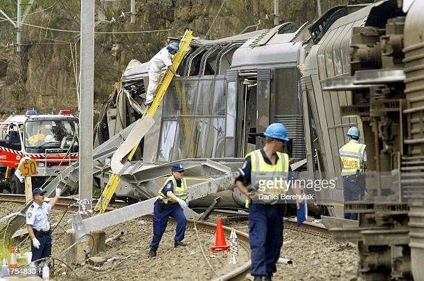 Police and rescue workers inspect a derailed commuter train January 31 2003 near the village of Waterfall south of Sydney Australia The Tangara...