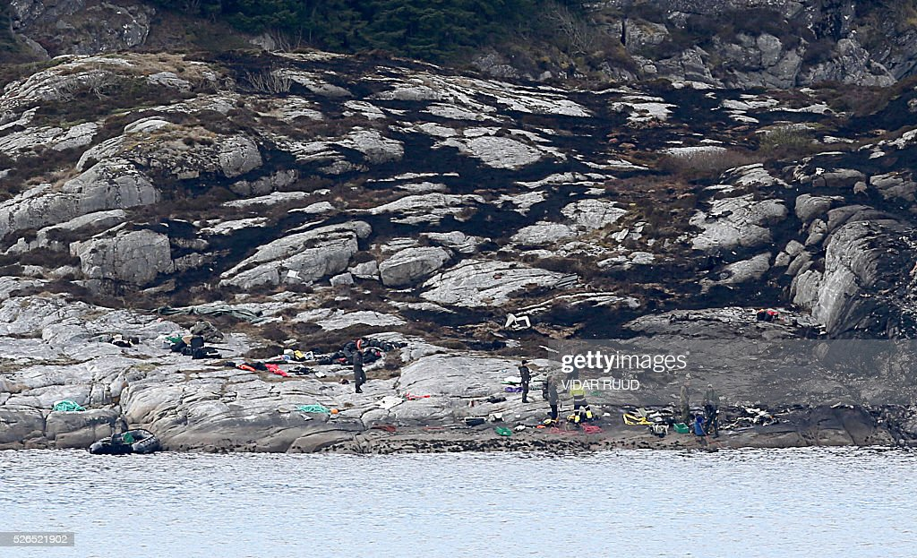 Police and rescue workers work at the site of a helicopter crash on the island Turoy on April 30, 2016. All 13 people on board a helicopter that crashed off the coast of western Norway died in the accident, rescue services said. / AFP / NTB scanpix AND NTB Scanpix / Vidar Ruud / Norway OUT