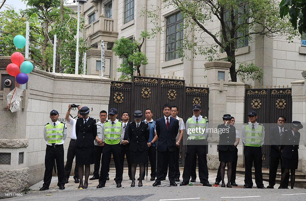 Police and security personnel keep vigil outside the home of Asia's richest man Li Ka-shing as dock workers gathered for a protest over a pay dispute and working conditions, in Hong Kong on April 21, 2013. The workers were demanding a 20 percent pay rise as the strike entered its 25th day, and called on Li to intervene in the impasse, which has drawn attention to the city's high living costs and wealth gap. Li's Hongkong International Terminals (HIT) has tried to distance itself from the dispute, saying the workers are not direct employees but were taken on by subcontractors, which set their own levels of pay. AFP PHOTO / Dale de la Rey
