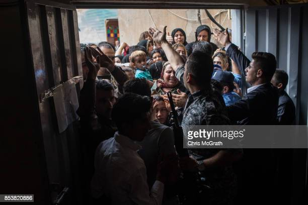 Police and security staff try to keep people from forcing their way into a voting station on September 25 2017 in Erbil Iraq Despite strong objection...