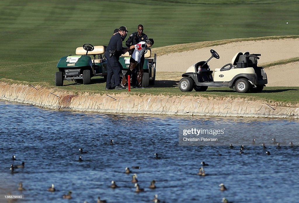Police apprehend a fan who swam the length of the pond on the 18th green during the final round of the Waste Management Phoenix Open at TPC Scottsdale on February 5, 2012 in Scottsdale, Arizona.