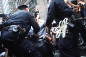 Police arrest a demonstrator associated with the 'Occupy Wall Street' movement as they march through the streets of the financial district and...