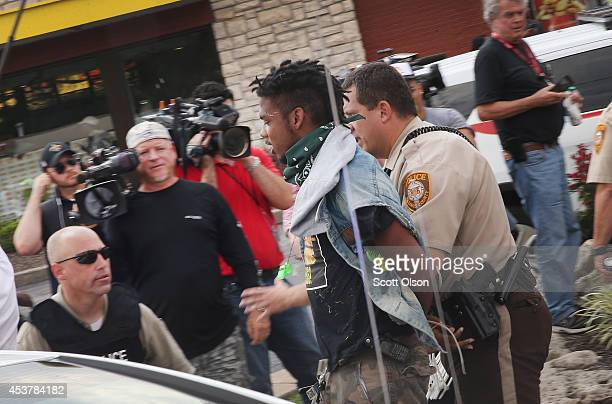 Police arrest a demonstrator protesting the killing of teenager Michael Brown on August 18 2014 in Ferguson Missouri After a protest yesterday ended...