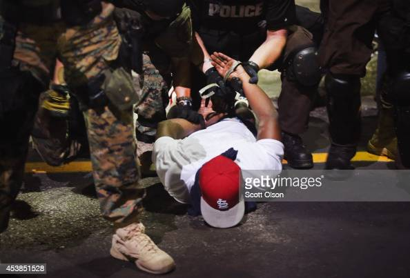 Police arrest a demonstrator protesting the killing of teenager Michael Brown on August 19 2014 in Ferguson Missouri Brown was shot and killed by a...