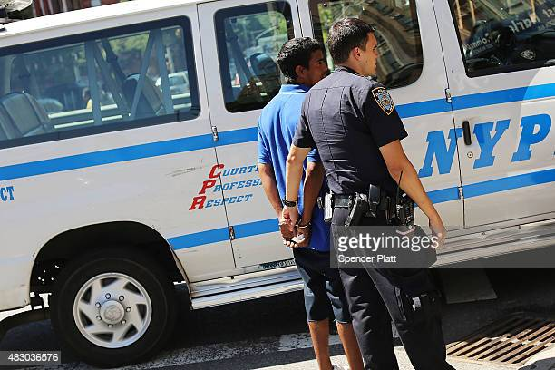 Police arrest a man in an area where people smoke K2 or 'Spice' a synthetic marijuana drug in East Harlem on August 5 2015 in New York City New York...