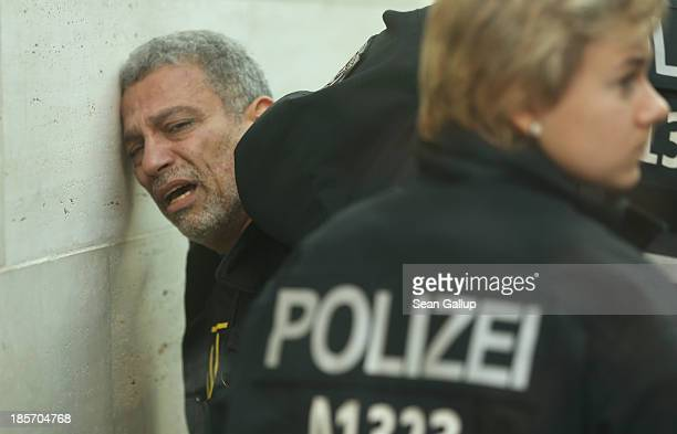Police arrest a man who was wearing a tshirt with slogans against foreign intervention in Egypt the Foreign Ministry on October 24 2013 in Berlin...
