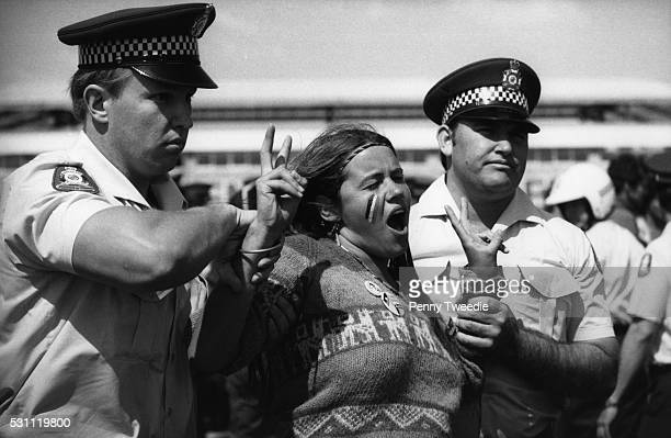 Police arrest a part Aboriginal woman during a demonstration for Aboriginal land rights at the 1982 Commonwealth Games in Brisbane
