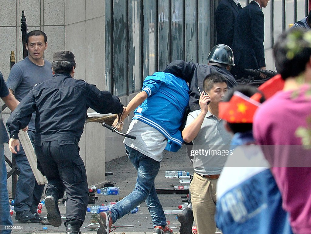 Police arrest a protester after a group through projectiles causing damage to a Japanese restuarant during a protest against Japan's 'nationalizing' of the disputed Diaoyu Islands, also known as Senkaku Islands in Japan in Xi'an, northwest China's Shaanxi province, on September 15, 2012. The protest, along with a series of other demonstrations across China, came after Japan this week announced it had bought the islands. CHINA