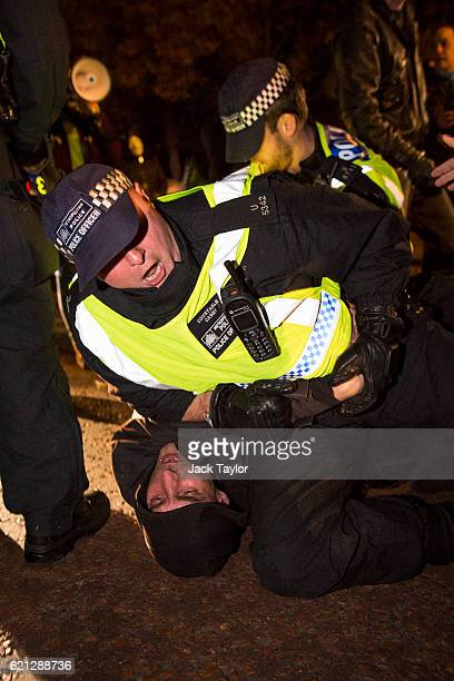 Police arrest a protester by Buckingham Palace during the Million Mask March on November 5 2016 in London England Thousands of demonstrators many...