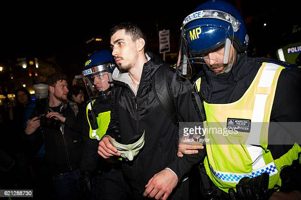 Police arrest a protester clutching a mask in Trafalgar Square during the Million Mask March on November 5 2016 in London England Thousands of...