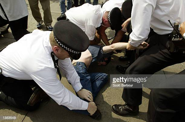 Police arrest a protester during the Rally for Islam organised by radical Islamic group AlMuhajiroun August 25 2002 at Trafalgar Square in London...