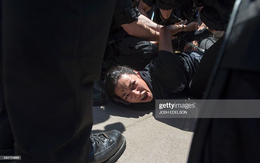 Police arrest a protester following a rally where republican presidential candidate Donald Trump spoke in Fresno, California on May 27, 2016. / AFP / JOSH