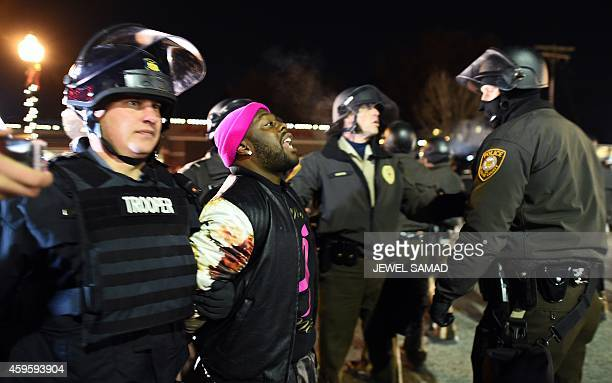 Police arrest a protester in Ferguson Missouri on November 25 2014 during a demonstration a day after violent protests and looting following the...