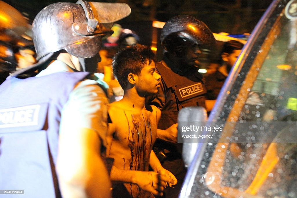 Police arrest a suspected one who was ran over from hotel injured with bullet in Dhaka, Bangladesh on July 02, 2016. Multiple foreigners are being held hostage by eight or nine gunmen at O'kitchen restaurant, in the same building as the the Holey Artisan Bakery cafe - a location popular with expatriates and diplomats. A gun battle between the attackers and police wounded three people, including two officers. Police and security forces have sealed off the area in the city's Gulshan district and are trying to negotiate a hostage release.