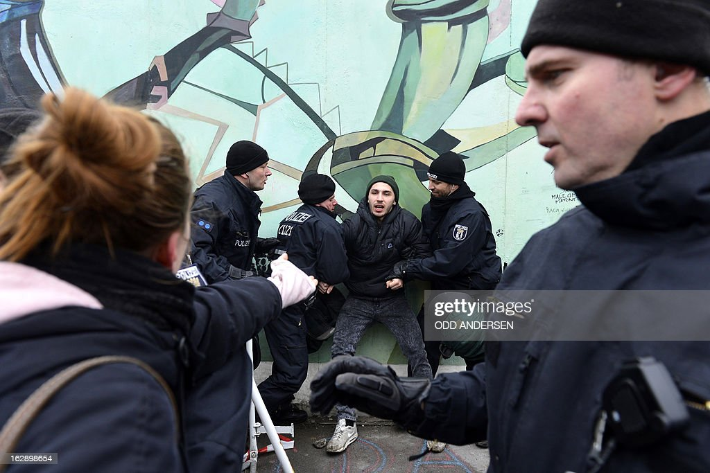 Police arrest an activist during a protest against the removal of a section of the East Side Gallery, a 1,3 km long remainder of the Berlin Wall, for a housing construction project near the city's east railway station in Berlin on March 1, 2013. Some 25 meters of this section of the wall that mostly came down 23 years ago and marked the end of the cold war are taken away to make way for a new housing development on river Spree, a project called Living Levels. As news of this spread activists and artists that had decorated this remaining part of the cold war relic known as the east side gallery came to protest.