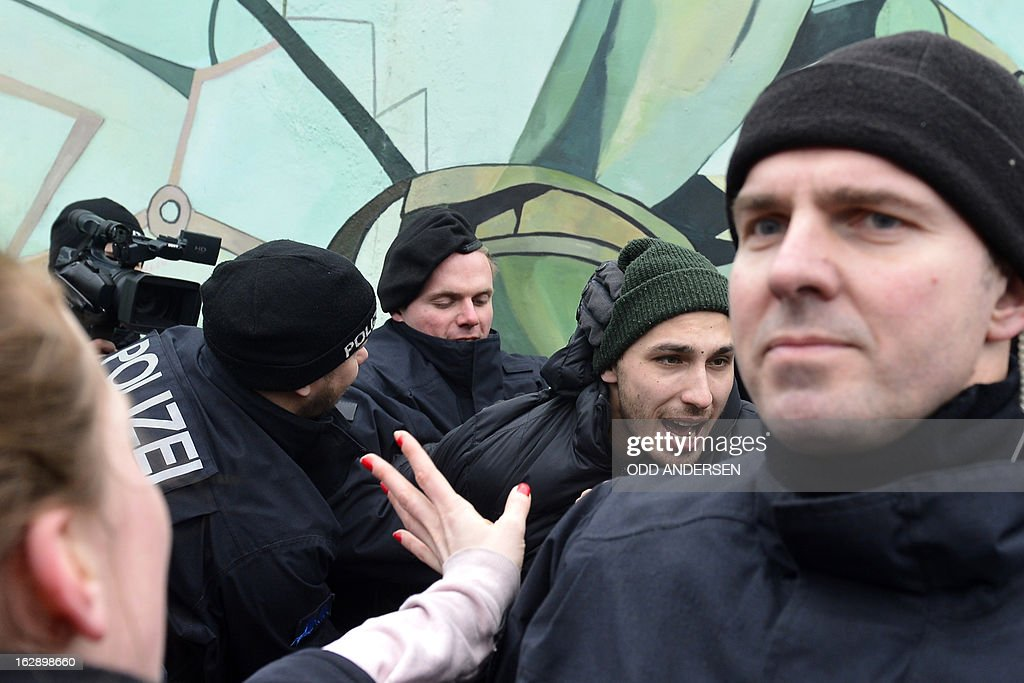 Police arrest an activist (C) during a protest against the removal of a section of the East Side Gallery, a 1,3 km long remainder of the Berlin Wall, for a housing construction project near the city's east railway station in Berlin on March 1, 2013. Some 25 meters of this section of the wall that mostly came down 23 years ago and marked the end of the cold war are taken away to make way for a new housing development on river Spree, a project called Living Levels. As news of this spread activists and artists that had decorated this remaining part of the cold war relic known as the east side gallery came to protest.