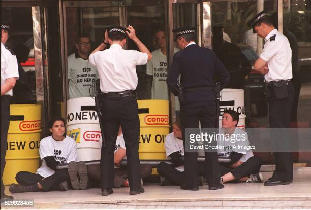 Police arrive to move on Greenpeace activists who formed a human chain to block the entrance to Conoco Oil's offices in central London this morning...