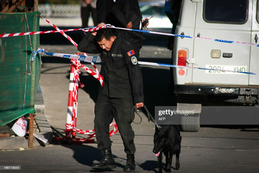 Police arrive with a dog to investigate the scene after nine Mongolian environmentalists protesting against legal changes which they say will loosen controls on mining were arrested outside parliament on September 16, 2013 after one fired a shot, in Ulan Bator. Leaders of the Fire Nation NGO coalition, which includes some nationalistic organisations, attempted to enter the building where the Great Hural was to meet for a special session but were stopped by guards, and a gunshot was heard, police said.