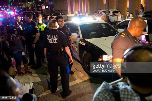 TOPSHOT Police attempt to calm the crowd as someone is arrested following the sniper shooting in Dallas on July 7 2016 A fourth police officer was...