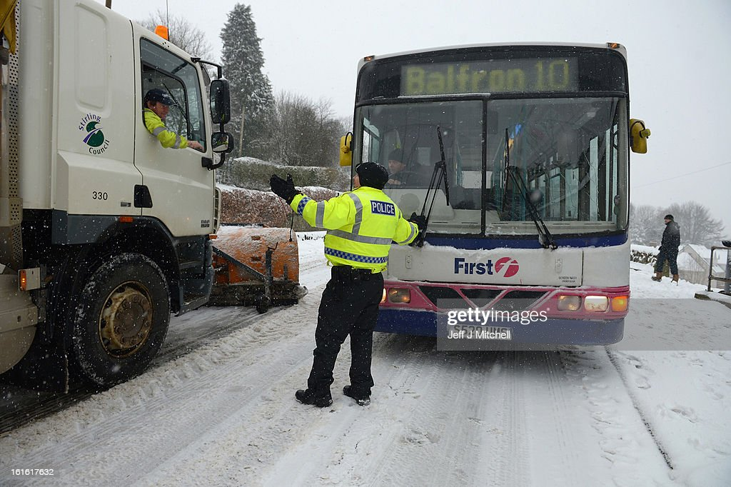Police attempt to clear traffic on February 13, 2013 in Blanefield, Scotland. Weather forecaster have issued a yellow weather warning of up to 10cm of snow on higher routes, with the possibility of travel disruption.