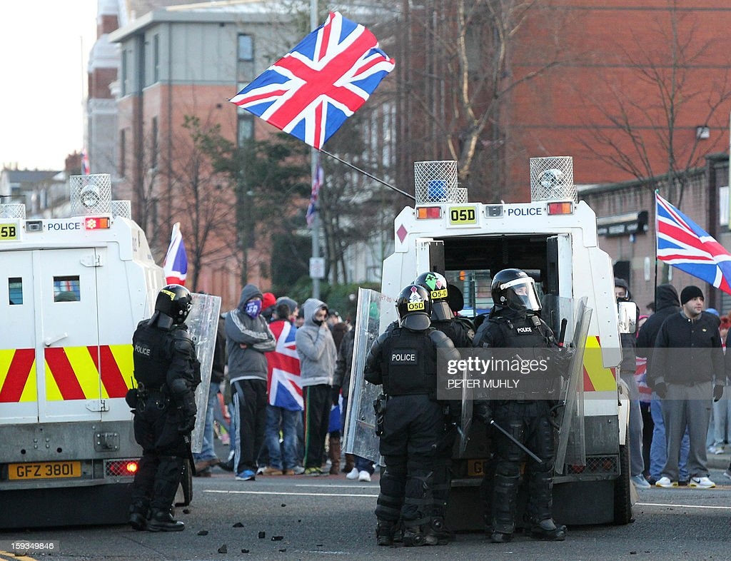 Police attempt to contain loyalist protesters waving Union Flags during violence between, loyalists, nationalists and the police in east Belfast, Northern Ireland on January 12, 2013 after the latest loyalist march against the decision to limit the days on which the Union Flag would be flown over Belfast City Hall. Northern Irish demonstrators loyal to Britain clashed with nationalists and police on Saturday in fresh protests against curbs on flying the British flag, leaving four officers injured, police said. The clashes were the latest to blight the British province after more than five weeks of violent disorder over the flag issue.