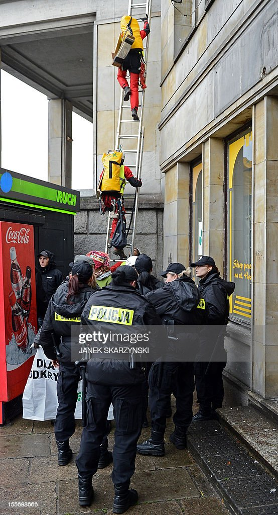 Police attempt to stop Greenpeace activists from draping Poland's Economy Ministry in Warsaw with protest banners against the development of new open pit coal mines in Poland which they argue will claim a high environmental and financial toll on November 7, 2012. AFP PHOTO/JANEK SKARZYNSKI