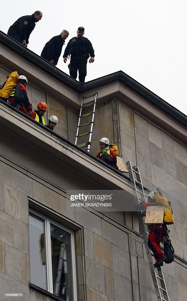Police attempt to stop Greenpeace activists from draping Poland's Economy Ministry in Warsaw with protest banners against the development of new open pit coal mines in Poland which they argue will claim a high environmental and financial toll on November 7, 2012.