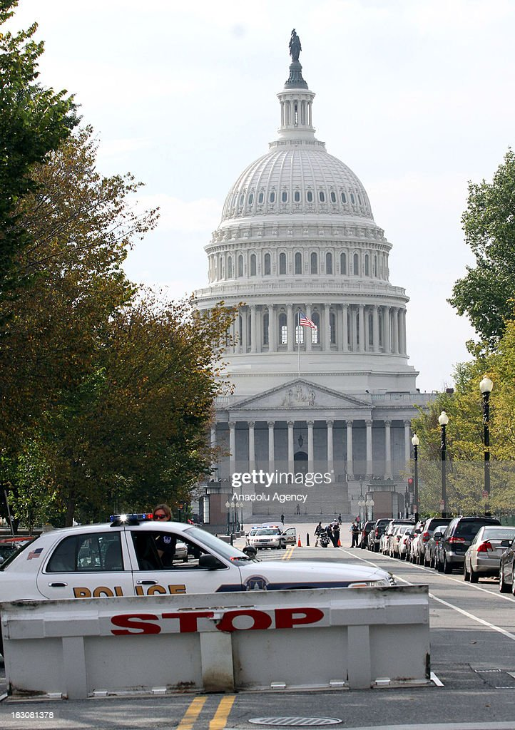 A police barricade blocks traffic around the U.S. Capitol on October 3, 2013 in Wasington. Washington police have put a Senate building on lockdown after gunfire was reported near the US Capitol. Eyewitnesses said many rounds were fired at Hart Office Building, prompting the police to cordon off the area and tell people in the neighborhood to stay inside.