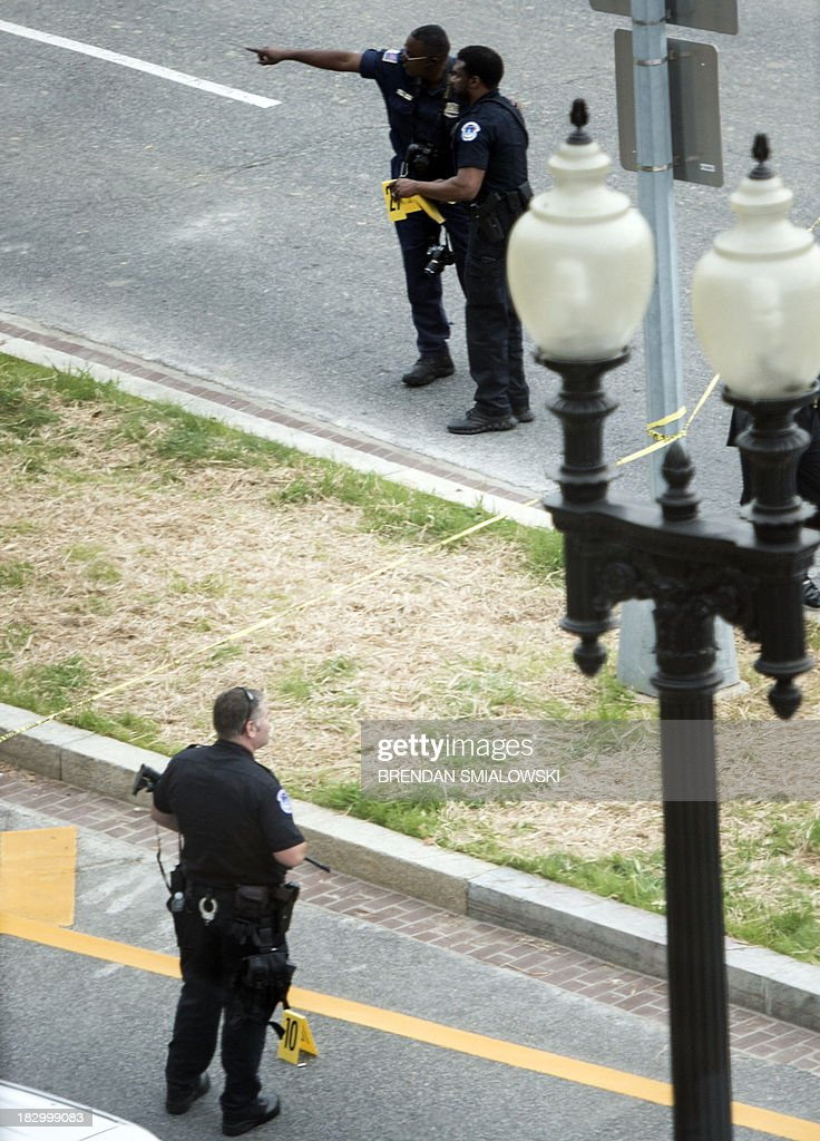 Police begin an investigation and place evidence markers on Constitution Avenue in front of Hart Senate Office Building on Capitol Hill October 3, 2013 in Washington, DC. Shots were reported as fired near 2nd Street NW and Constitution Avenue on Capitol Hill. About half an hour after the incident began, the security lockdown at the Capitol was eased and the doors reopened. AFP PHOTO/Brendan SMIALOWSKI