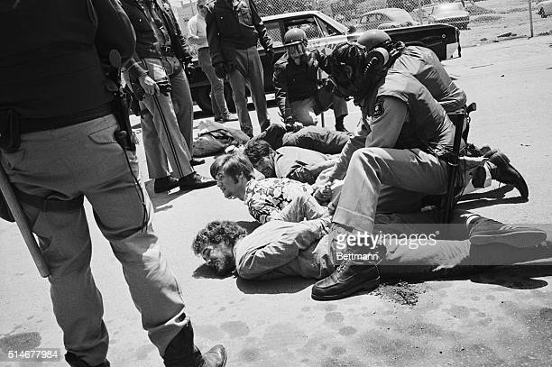Police bind the hands of demonstrators who were subdued during a clash with 2 000 demonstrators marching on a University of California at Berkeley...