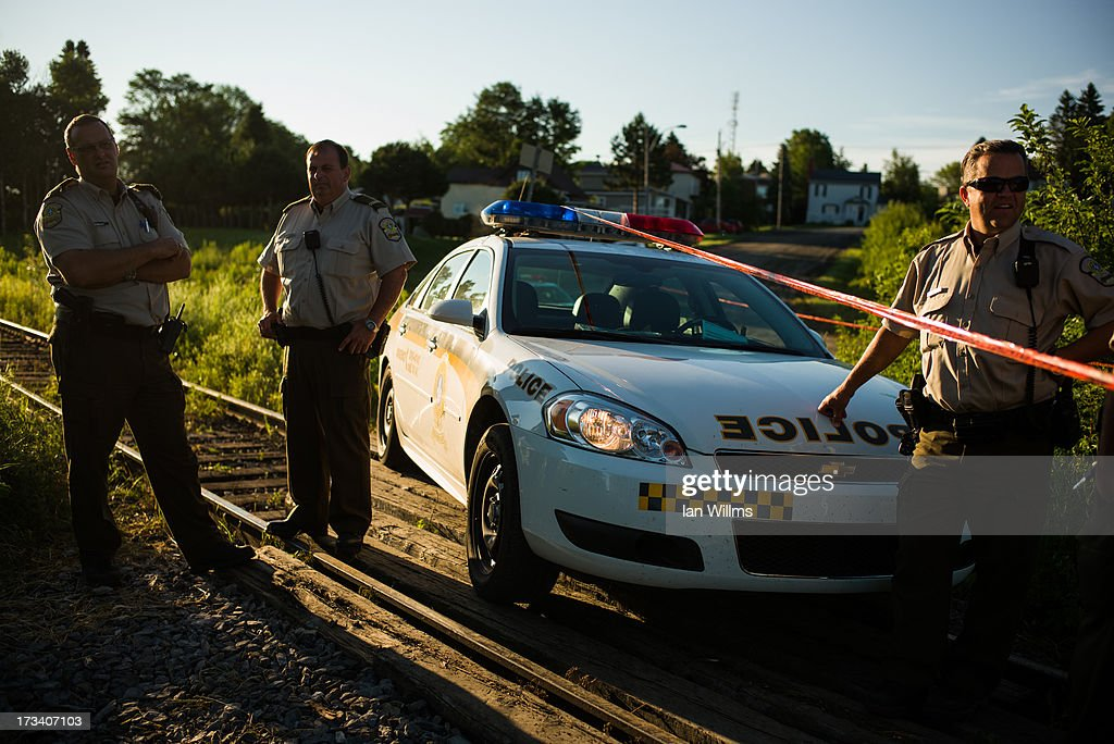 Police block a section of railway tracks, July 13, 2013 in Lac-Megantic, Quebec, Canada. A train derailed and exploded into a massive fire that flattened dozens of buildings in the town's historic district, leaving 60 people dead or missing in the early morning hours of July 6.