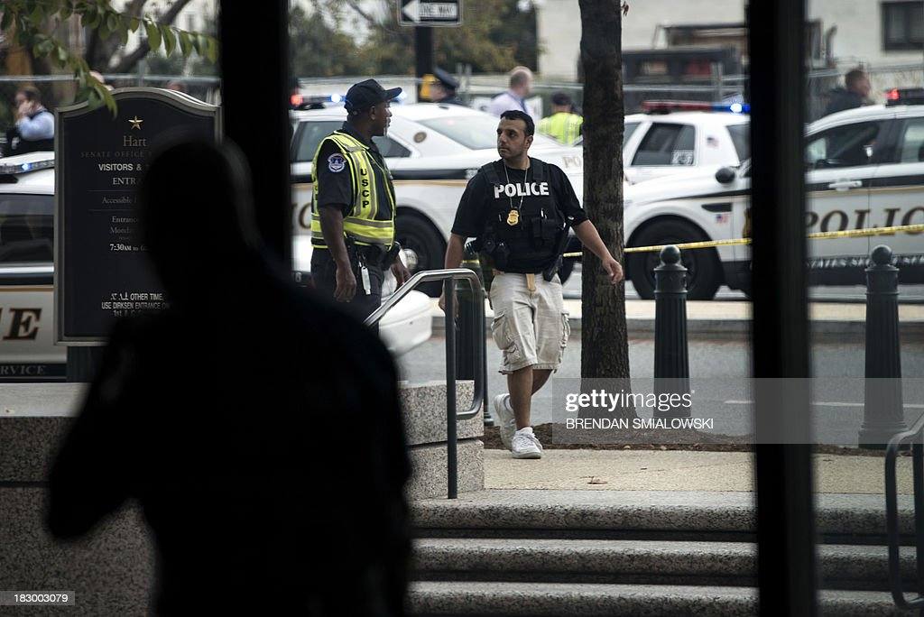 Police block off the Hart Senate Office building's entrance to Constitution Avenue on Capitol Hill October 3, 2013 in Washington, DC. Shots were reported as fired near 2nd Street NW and Constitution Avenue on Capitol Hill. AFP PHOTO/Brendan SMIALOWSKI