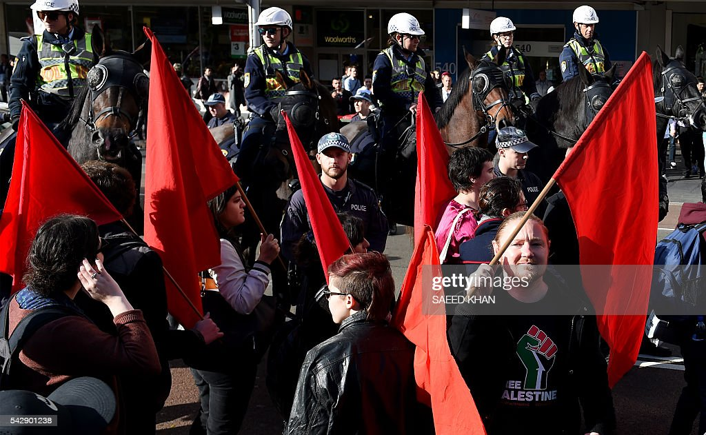 Police block the way of pro-gay marriage supporters to avoid any clash with an anti-gay group in Sydney on June 25, 2016. Hundreds of supporters of gay marriage marched through the streets of the central business district of Sydney for their rights. / AFP / SAEED