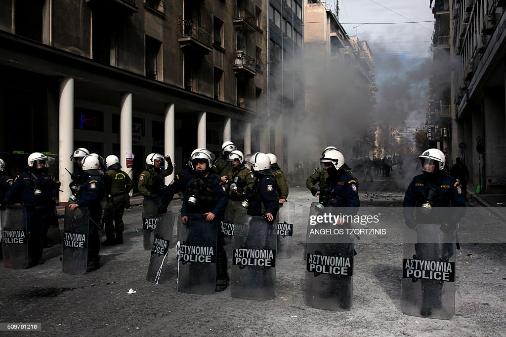 Police blocking the entrance to the Agriculture ministry in Athens, during a demonstration against the pension reform on February 12, 2016. Fears that Greece will exit the eurozone, a 'Grexit', could revive if Greek authorities do not come up with 'credible' reforms, notably on pensions, a senior IMF official said February 11, 2016. / AFP / ANGELOS TZORTZINIS