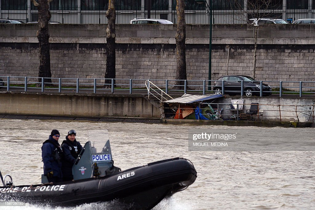 A police boat passes a shanty house in Paris on December 26, 2012. AFP PHOTO / Miguel Medina