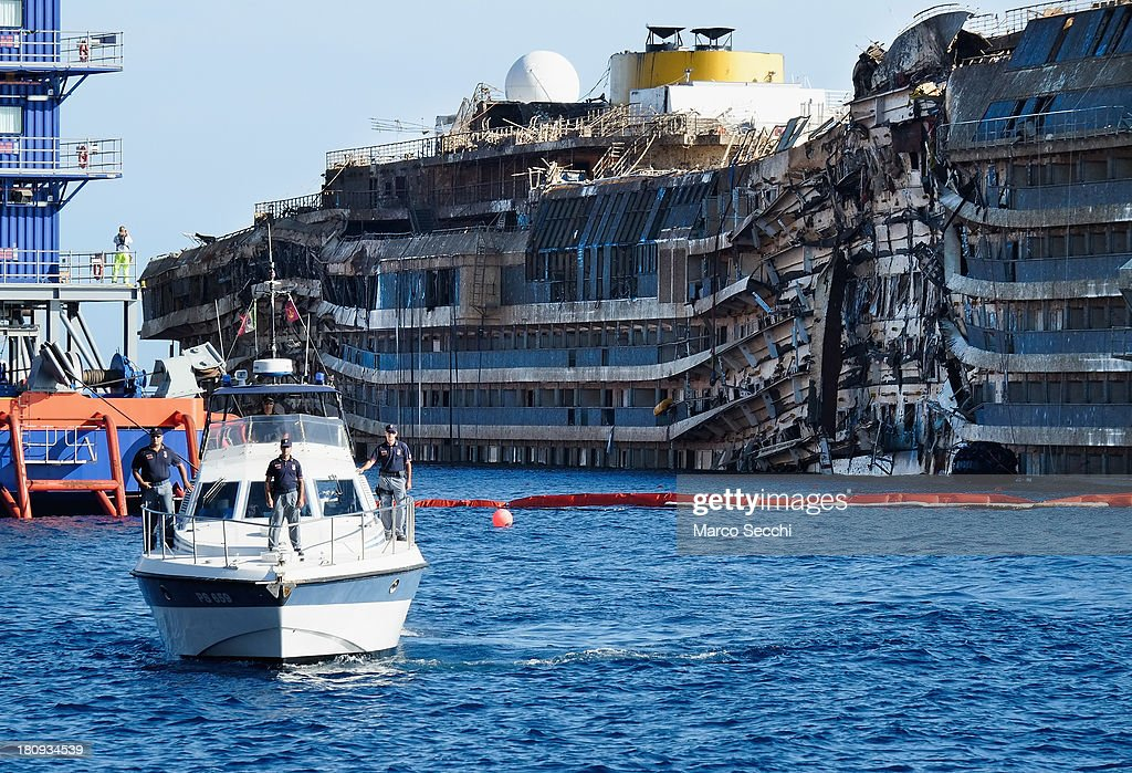 A police boat patrols in front of the severely damaged right side of the Costa Concordia cruise ship on September 18, 2013 in Isola del Giglio, Italy. The vessel, which sank on January 12, 2012, was successfully righted during a painstaking operation yesterday morning. The ship will eventually be towed away and scrapped. It was the first time the procedure, known as parbuckling, had been carried out on a vessel as large as Costa Concordia.