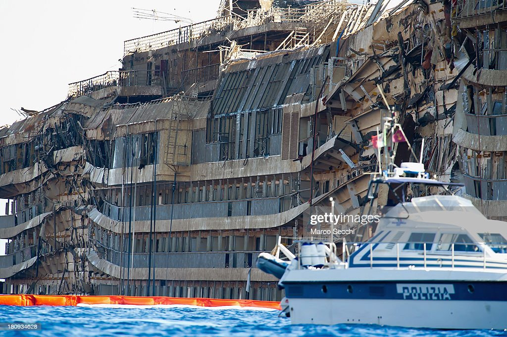 A police boat patrols in front of the severely damaged right side of the upright Costa Concordia cruise ship on September 18, 2013 in Isola del Giglio, Italy. The vessel, which sank on January 12, 2012, was successfully righted during a painstaking operation yesterday morning. The ship will eventually be towed away and scrapped. It was the first time the procedure, known as parbuckling, had been carried out on a vessel as large as Costa Concordia.