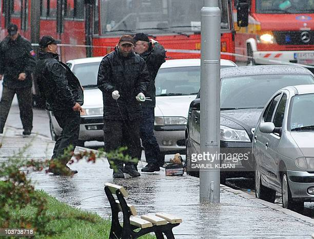 Police bomb expert joke around next to a fake bomb placed near a parked car on August 31 2010 in the Bratislava suburb of Devinska Nova Ves after a...