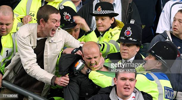 Police break up fighting in the stands between Wigan and Liverpool fans during the Premier league football match at the JJB Stadium Wigan northwest...