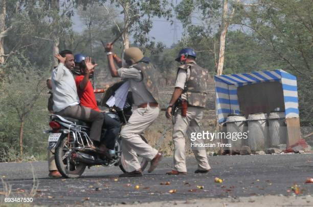 Police cane charge on commuters on the MhowNeemuch highway on June 7 2017 in Mandsaur India More than a dozen policemen were injured one critically...