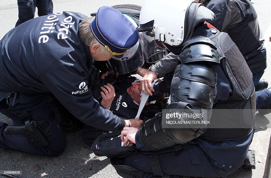 Police captain Pierre Vandersmissen is injured after being hit in the head during a national anti-austerity demonstration on May 24, 2016, in Brussels. Belgian trade unions called for mass protests against the centre-right government's proposed work reforms as they plan rallies and strikes over the next few months. / AFP / BELGA / Nicolas MAETERLINCK / Belgium OUT