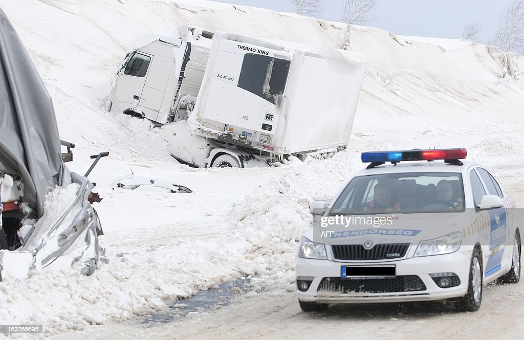 A police car arrives at the site of an accident involving a truck and cars at the E71 motorway, nearby the Croatian, Slovenian and Hungarian borders on March 15, 2013 a day after a heavy snow storm hit the area. A cold snap that caused havoc elsewhere in Europe sent temperatures plunging and blanketed large parts of Hungary in snow, causing major transport problems and leaving tens of thousands without electricity. GERGELY