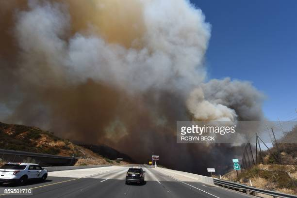 TOPSHOT A police car blocks the 241 freeway as smoke from the Canyon 2 Fire covers the freeway near Orange California October 9 2017 in Orange...